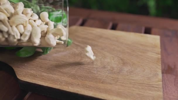 Cashew nuts falls on the wooden board, ingredients for pesto sauce, vegetarian food, diet and healthy meals