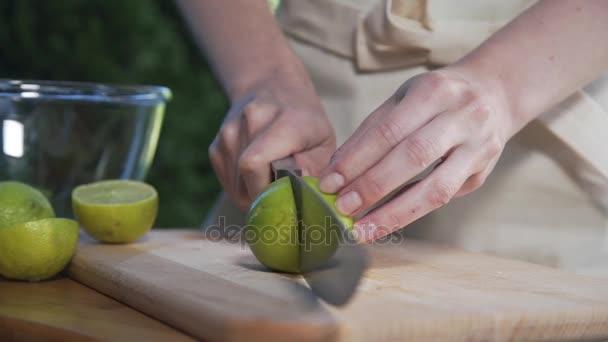 Hospodyňka kusy vápna v polovině s ostrým nožem na dřevěné desce venku, vaření venku, zeleninu a ovoce, vitamíny a zdravá výživa