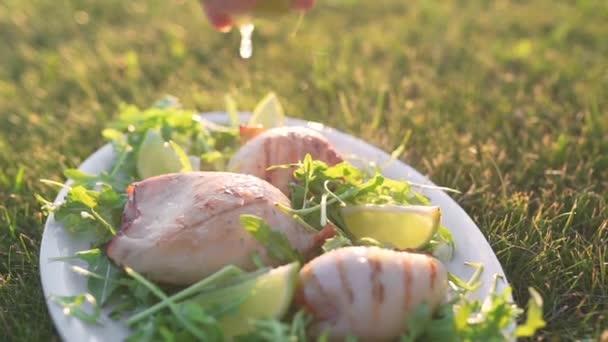 Zakouřený pražené olihně se kropení s citronovou šťávou a leží na talíři s čerstvou zelení na trávě v západu slunce světlo, vaření venku, gril a gril, takže plody jídla na otevřeném ohni