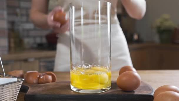 Kuchař rozbije vejce pro výrobu těsta, dorty chleba a pečiva, vaření s vejci, jídlo v kuchyni
