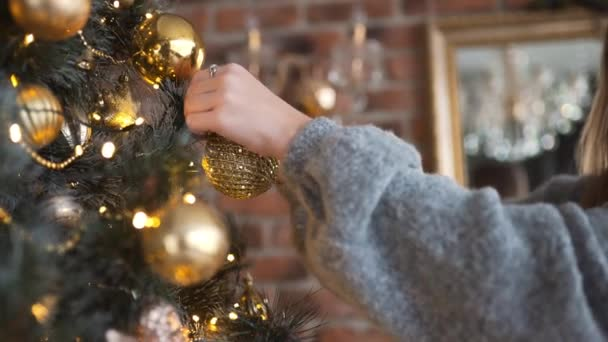 Young attractive caucasian woman decorates Christmas tree by gold balls, christmas eve, x-mas arrangements, garlands and decor for winter holidays