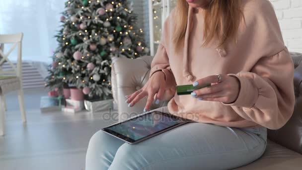 Žena sedí na pohovce a dělá nákupy na internetu s tabletem zadáním její informace o kreditní kartě, on-line plateb, on-line nákupy, dívka sedí na pohovce a kupuje zboží online