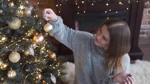 Mladá atraktivní Kavkazský žena zdobí vánoční strom zlaté kuličky, Štědrý večer, vánoční uspořádání, věnce a výzdoba pro zimní dovolenou