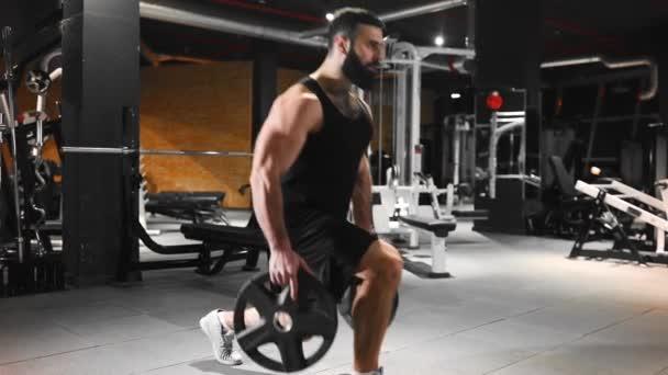 Muž pumpuje svaly v posilovně, silová cvičení, sportovec na fitness klubu, Kavkazský muž s plnovousem pumpuje svaly, chlap s fit tělo a velké svaly, zdraví a krása