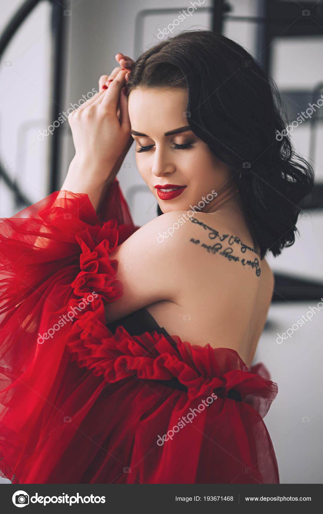 5dab24fca90d Elegante donna attraente con il tatuaggio sulla sua spalla in abito  splendido lunga notte
