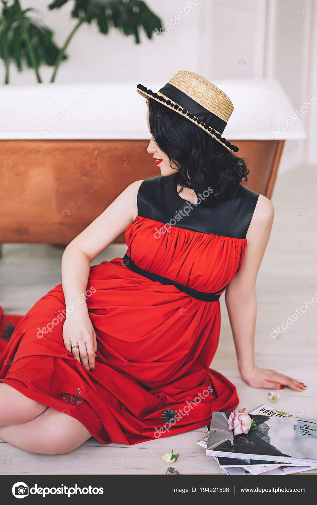 2d0f97dd94eb Moda ritratto di signora incinta elegante attraente in sarafan rossi lunghi  e cappello di paglia