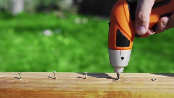 Muž využití elektrické nástroje pro šroubování šroubů nenatřeného dřevěný blok, šroubovák v použití ve venkovním prostoru, ručně dělané a Diy věci, práce se dřevem, vyřešení problémů s objekty