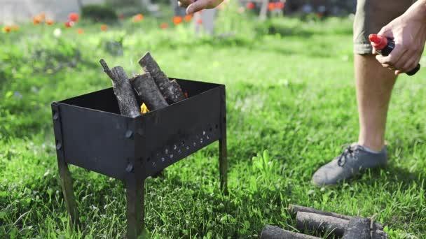 Člověk hodí dříví na oheň, grilování na zahradě, takže žhavé uhlíky pro vaření na otevřeném ohni, letní grilování