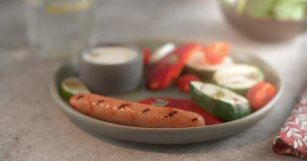 Pečená klobása se dává na talíř s grilovanou zeleninou vidličkou ve zpomaleném filmu, grilované klobásy, párky v rohlíku s masovými výrobky, vařené kuře, 4k 60p 10 bit Prores HQ 422