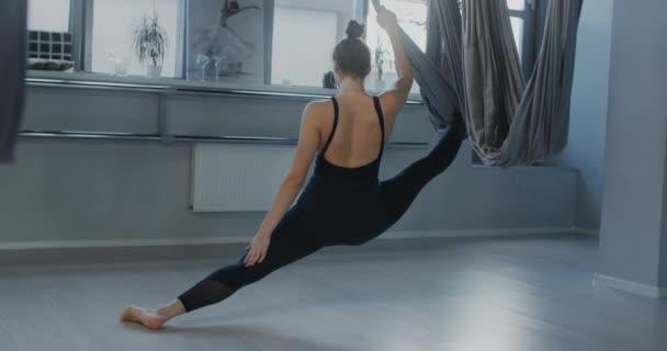 Atraktivní mladá žena sedí na motouzu v houpací síti s jógou ve zpomaleném filmu, flexibilní žena dělá akrobatická a plastická cvičení, jóga a strečink, 4k DCI 60p Prores 422