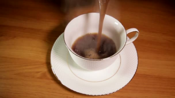 Hot coffee is pouring into a coffee cup.