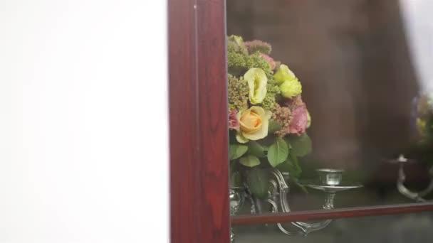 Dvě zdobené stříbrnými svícny s květy přes okenní sklo. Krásné svatební obřad