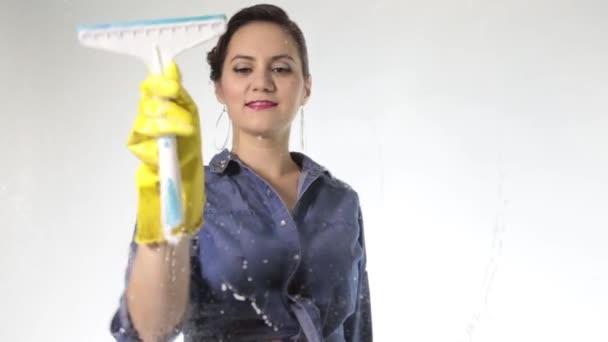 junge Hausfrau Fenster mit einem Spray, Tuch und Reinigungsmittel gewaschen. Großes Glas im Schaum. Hausarbeit-Konzept.