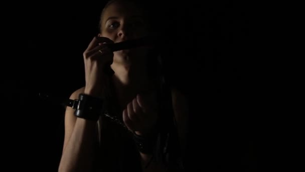 beautiful naked woman in handcuffs holding a whip on black background. BDSM concept