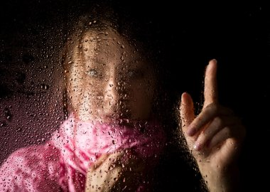 young sad woman portrait behind the window in the rain with rain drops on it