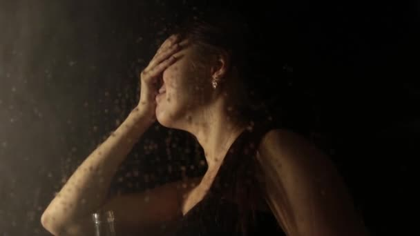 junge traurige Frau hinter dem Fenster mit Tropfen darauf. einsame Mädchen trinken Schnaps aus der Flasche und weinen