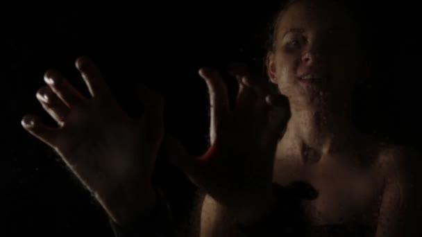 gyönyörű meztelen nő látható bilincs a kezét a fekete háttér. Lány mögött az üveg és a víz csepp rajta. BDSM koncepció