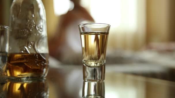 Vértes pohár konyakot vagy whiskyt, fiatal szexi pár ágyban átöleled, és. homályos fókusz, szerelmesek a háttérben ágyon