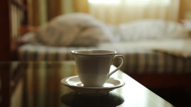closeup cup of hot tea or coffee, young sexy woman waking up stretching arms on the bed in the morning. blurred focus