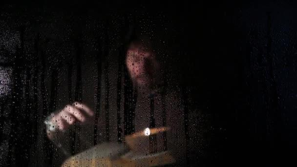 Nekromanta varázslatok vastag ősi könyvből vet gyertyafénynél, átlátszó üveg víz csepp a sötét háttéren szereplő mögött