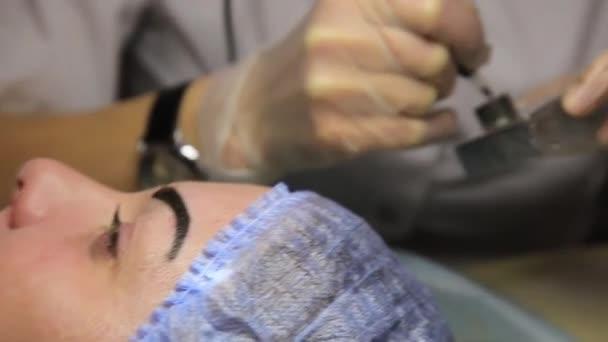 Anwendung von permanent Make-up Kosmetikerin. Schöne alte, kosmetische Tätowierung auf ihrer Augenbraue. Beauty-Salon für Frauen. Kosmetische Tätowierung