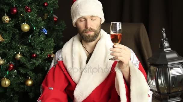 böser brutaler Weihnachtsmann trinkt Wein und gratuliert zum Feiertag, zum Hintergrund des Weihnachtsbaums