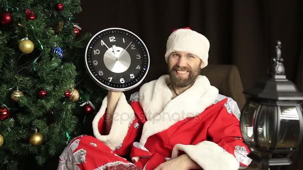 špatný brutální Santa Klaus s úsměvem a ukazuje hodiny, pět minut před dvanáctou, na pozadí vánočního stromu