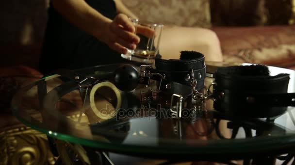junge Frau trinken Schnaps und nimmt den Knebel. Closeup Bdsm Accessoires und Sex-Spielzeug