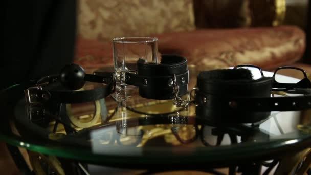junge Frau nimmt Gläser und Handschellen. Closeup Bdsm Accessoires und Sex-Spielzeug