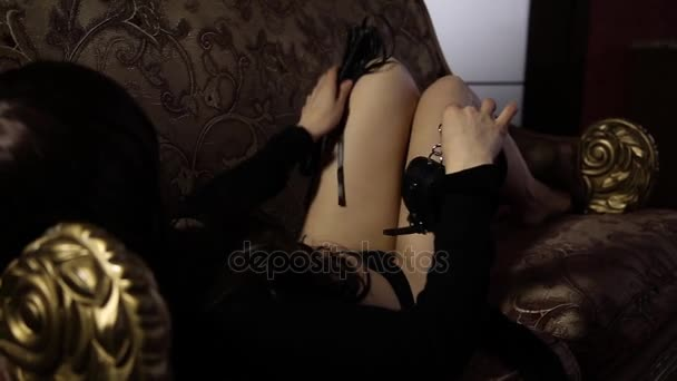 Seductive Woman Lying On A Couch Holding Whip Bdsm Concept Accessories And Sex