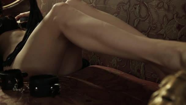 seducente donna sdraiata su un divano, tenendo frusta. BDSM concetto, accessori e sex toys