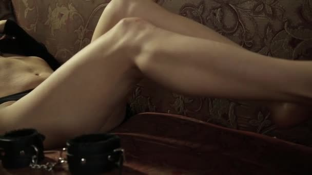 verführerische Frau auf einer Couch, hält Peitsche. BDSM-Konzept, Accessoires und Sex-Spielzeug
