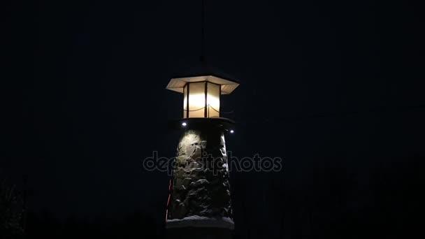 Maják blikající a Spinning v noci. Světelná signalizace pro lodě a čluny