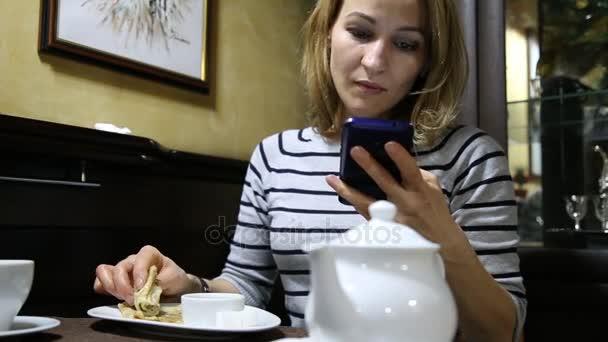 Žena jí lahodné horké palačinky a mluví telefonu