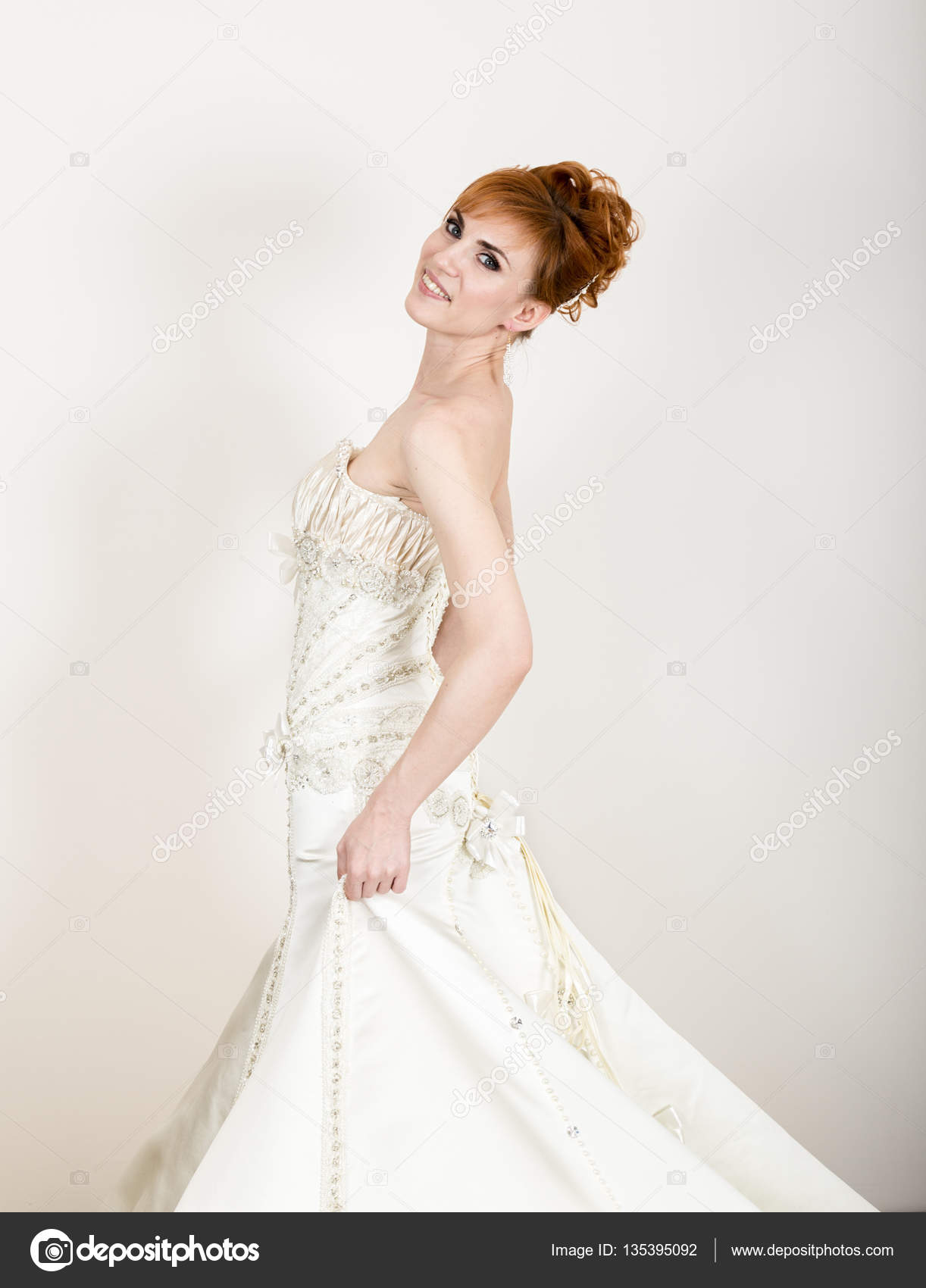Beautiful young redhead bride wearing white wedding dress with beautiful young redhead bride wearing white wedding dress with professional make up and hairstyle junglespirit Choice Image