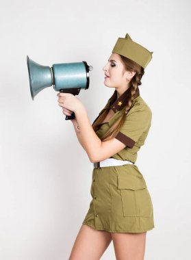 sexy fashionable woman in military uniform and garrison cap, holding bullhorn and screaming