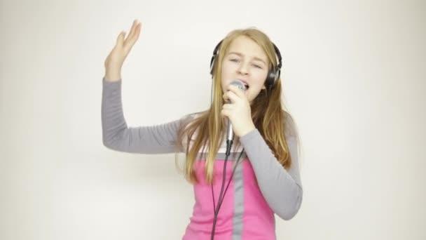 junges Mädchen hört Musik über Kopfhörer, hält Mikrofon in der Hand, singt und tanzt
