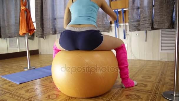 schöne Fitness-Frau mit durchtrainiertem Körper, die auf dem Fitnessball sitzt und Übungen macht. Zeitlupe