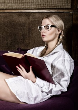 Young woman with pigtails in mans shirt over his naked body, reading a book sitting on a sofa