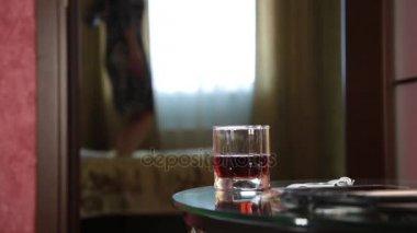 fiatal részeg arab lány vicces ugrás az ágyon. közeli pohár pálinka
