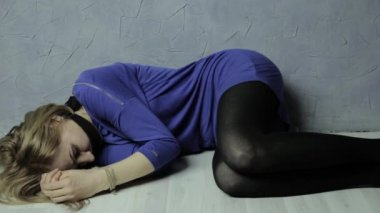 frightened girl gagged lies on the floor with tied hands, next is a kidnapper with bat. kidnapping and violence