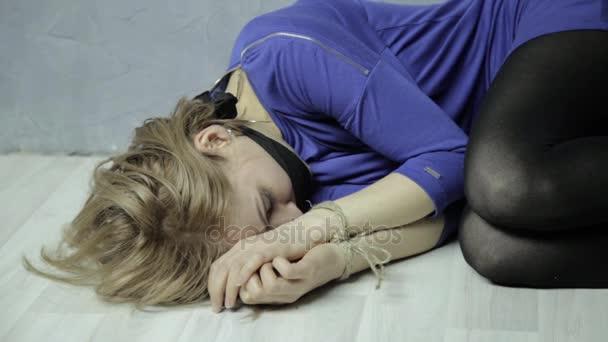 rémült sír lány öklendezett, fekszik a földön kötött kézzel. emberrablás és az erőszak