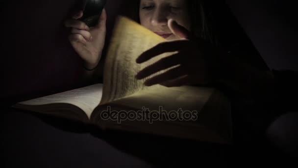 mladá dívka pomocí baterku ve tmě pro čtení knihy pod dekou