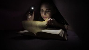 Brother and sister read a book under a blanket with a flashlight in young girl using flashlight in dark for reading book under the blanket sciox Gallery