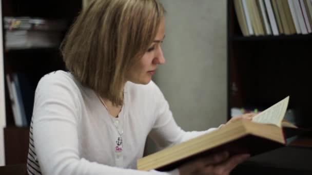 mladá žena s velkou knihou v knihovně. regály s knihami