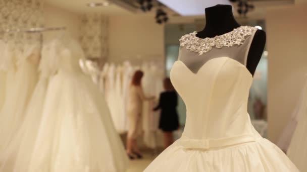 Közeli kép: dummy esküvői ruha. Elárusítónő segíti a csinos, fiatal nő egy esküvői ruha kiválasztása. Homályos középpontjában a háttérben.