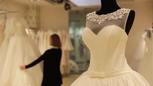 gyönyörű fiatal nő választott egy esküvői ruha, esküvői butik. Homályos középpontjában a háttérben. Közeli kép: dummy esküvői ruha.