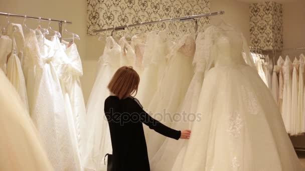 9ca9baa2a4 Hermosa joven novia elegir un vestido de novia en una boutique de novia–  metraje de stock