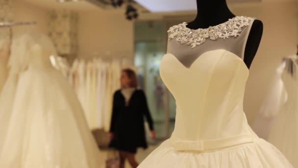 közeli kép: esküvői ruha, fiatal gyönyörű nő választott egy fehér ruha, esküvői Shop próbabábu.