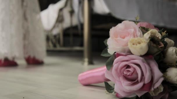 Detail Dámská obuv a svatební kytice na podlaze. První svatební noc. Nevěsta přichází k posteli, odstraňuje boty a krajkové šaty